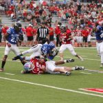 Blue player tackling a red player.