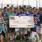 Players presenting Tanner Cook a check.